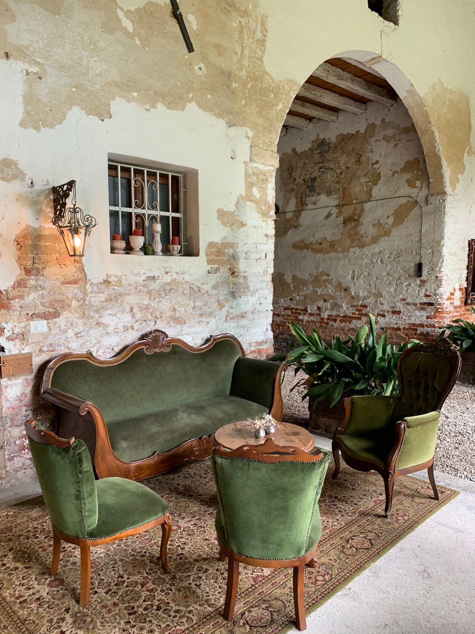 Un piccolo salotto verde, fatto apposta per il relax e le chiacchiere all'interno del Casale nel Glamping Canonici di San Marco