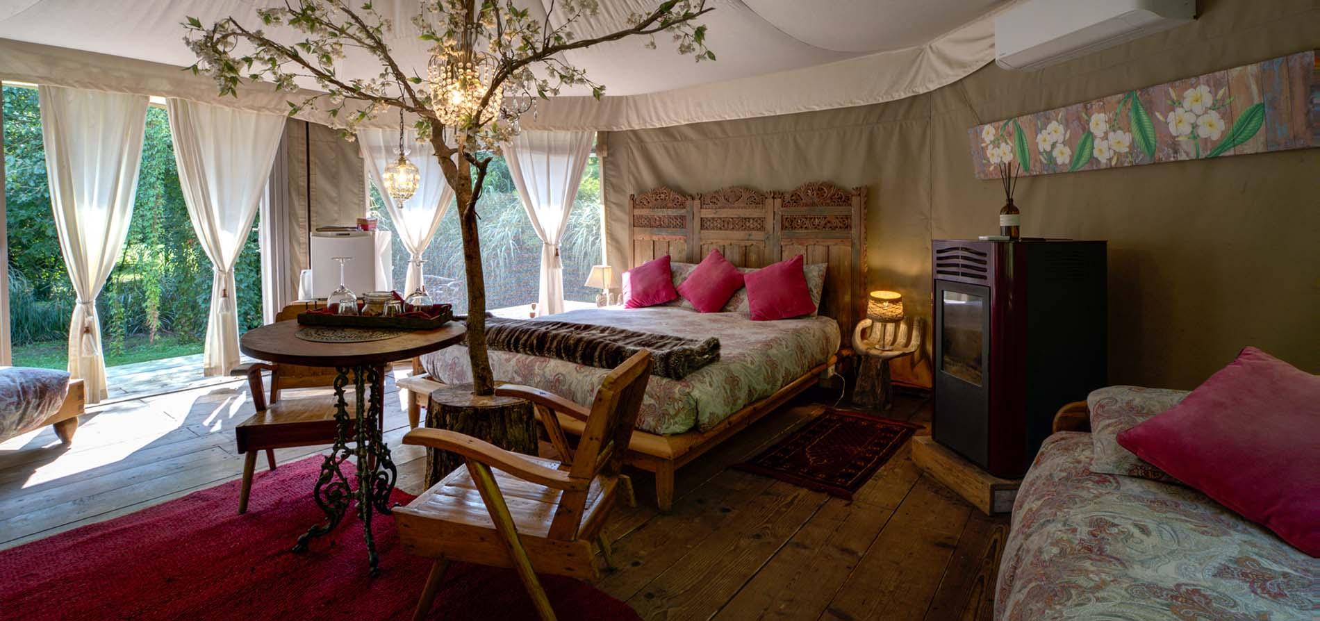 Ampia vista sulla natura, luci glamour e un albero fiorito all'interno di una luxury tent del Glamping Canonici