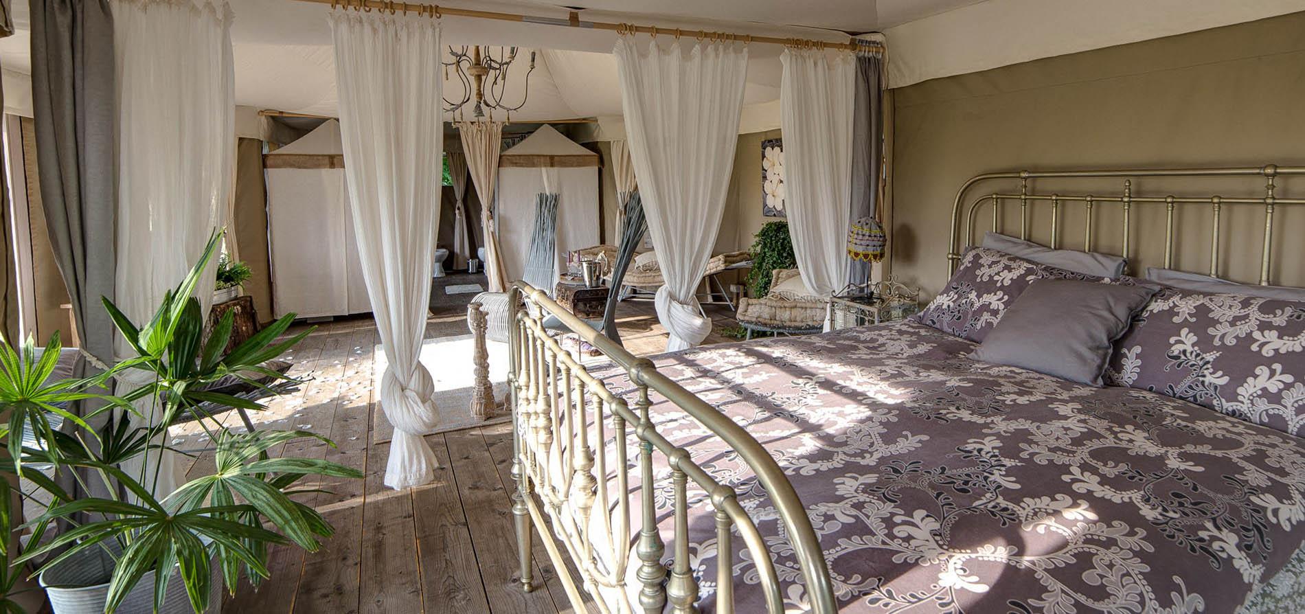 La zona notte della suite-tent del Glamping con un lussuoso letto matrimoniale