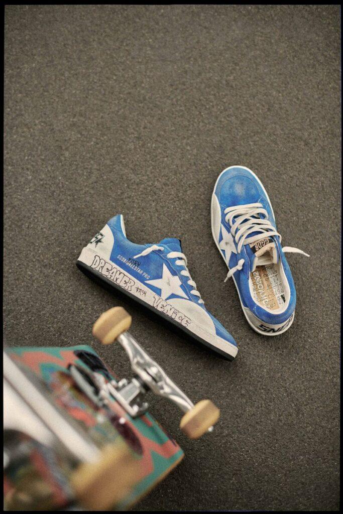 Le sneakers azzurre Golden Goose accanto allo skateboard di Cory Juneau