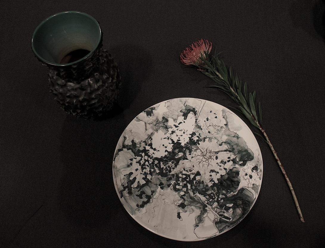 Un decoro in cui le macchie monocromatiche sembrano acquarelli in movimento sul piatto in ceramica dipinto da Chiara Bernardini